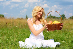Girl with fruit. Beautiful smiling blonde with a basket of fruit stock images