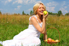 Girl with fruit. Beautiful smiling blonde with a basket of fruit royalty free stock photo