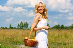 Girl with fruit. Beautiful smiling blonde with a basket of fruit Royalty Free Stock Photography