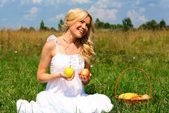 Girl with fruit. Beautiful smiling blonde with a basket of fruit royalty free stock photos