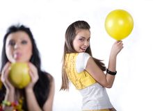 Girl with fruit and girl with yellow balloon Royalty Free Stock Photos