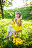 Girl with fruit on a green lawn Stock Image