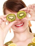 Girl in fruit necklace covering eyes with kiwi Stock Photos