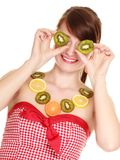 Girl in fruit necklace covering eyes with kiwi Stock Images