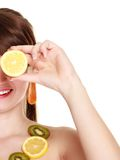Girl in fruit necklace covering eyes with lemon Stock Photo