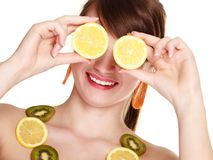 Girl in fruit necklace covering eyes with lemon Stock Images