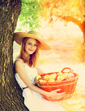Girl with fruits in basket at garden. Stock Image