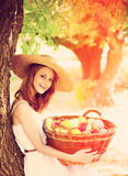 Girl with fruits in basket at garden. Stock Photos