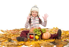 Girl with fruits and vegetables on autumn leaves Stock Photography