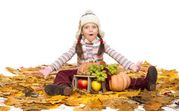 Girl with fruits and vegetables on autumn leaves Royalty Free Stock Photos