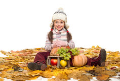 Girl with fruits and vegetables on autumn leaves Stock Photo
