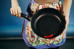 The girl with a frying pan. Are red sharp Chile pepper on a frying pan stock photos