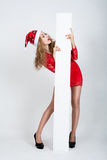 Girl in full growth in a Christmas hat holding banners. Royalty Free Stock Photography