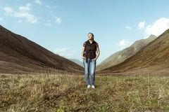 Girl full-length in the mountains with a backpack stock photo