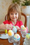 The girl is fun painting eggs for Easter royalty free stock photography