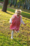 Girl fun runs in the park Stock Photography