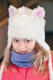 Girl in fun white artificial fur hat Royalty Free Stock Images