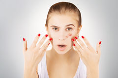 Girl with acne, grey gradient background. Girl with funny disgusted face examines her pimples royalty free stock images