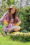 Girl with funny expression looks at flowers Royalty Free Stock Photography