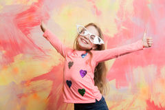 Girl in funny eyeglasses smiling with two thumbs up. Gestures on colorful abstract wall. Happy model with blond hair posing in fashionable clothes. Child Stock Photo