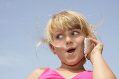 Girl with funny face on cell phone. A young girl is doing a funny face while talking on her touch phone Stock Photos