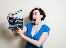 Girl with funny face and movie clapper on white background Royalty Free Stock Images