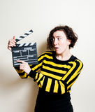 Girl with funny face and movie clapper on white background Royalty Free Stock Photos
