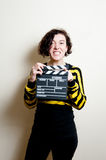 Girl with funny face and movie clapper on white background Royalty Free Stock Photography