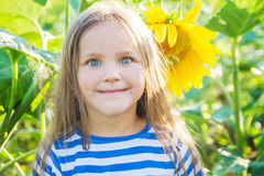 Girl with funny face among sunflower filed Royalty Free Stock Images