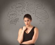 Girl with funny facial expression. A cute female student making funny expressions with thoughts in her head illustrated by drawn chat bubbles on the urban wall Royalty Free Stock Image