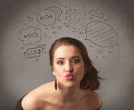 Girl with funny facial expression. A cute female student making funny expressions with thoughts in her head illustrated by drawn chat bubbles on the urban wall Stock Photo