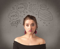 Girl with funny facial expression. A cute female student making funny expressions with thoughts in her head illustrated by drawn chat bubbles on the urban wall Royalty Free Stock Photo