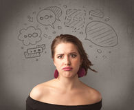 Girl with funny facial expression. A cute female student making funny expressions with thoughts in her head illustrated by drawn chat bubbles on the urban wall Stock Photos