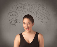 Girl with funny facial expression. A cute female student making funny expressions with thoughts in her head illustrated by drawn chat bubbles on the urban wall Stock Image