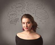 Girl with funny facial expression. A cute female student making funny expressions with thoughts in her head illustrated by drawn chat bubbles on the urban wall Royalty Free Stock Images
