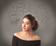 Girl with funny facial expression. A cute female student making funny expressions with thoughts in her head illustrated by drawn chat bubbles on the urban wall Stock Photography