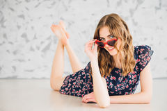 Girl in funny glasses on a floor Royalty Free Stock Images