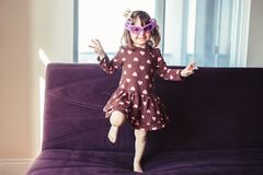 Girl with funny glasses jumping dancing on couch indoors. Portrait of cute adorable little girl with funny glasses jumping dancing on couch indoors. Preschooler Royalty Free Stock Photography