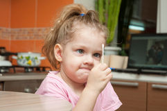 Girl with a funny looking angrily at a cotton swab Royalty Free Stock Images