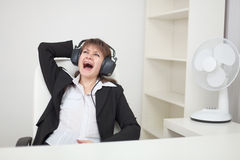 Girl funny sings sitting in an armchair at office Stock Images