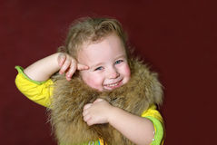 Girl with fur. Beautiful little girl with fake fur Royalty Free Stock Photography