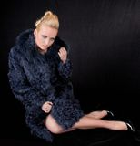 Girl in a fur coat. On a black background Stock Photo