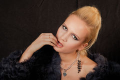 Girl in a fur coat. On a black background Royalty Free Stock Image
