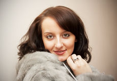 GIRL IN A FUR COAT. Beauty Girl with brown hair in a fur coat Royalty Free Stock Photography