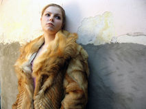 The girl in a fur coat. Costs near a wall Royalty Free Stock Photos
