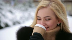 Girl in fur coat drinks coffee in the winter Park. stock video footage