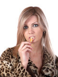The girl in  fur coat eats  tangerine Royalty Free Stock Photography