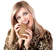 The girl in a fur coat gnaws coconut Stock Photography