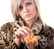 The girl in  fur coat holds  hand  tangerine Royalty Free Stock Image