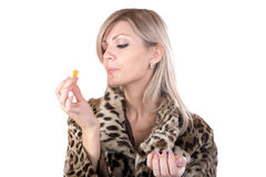 The girl in  fur coat holds in hand  tangerine Stock Photos